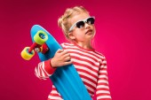 stylish kid in sunglasses posing with skateboard isolated on red