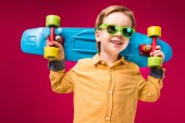 stylish smiling boy in sunglasses posing with penny board isolated on red