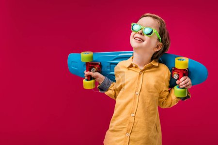 Photo for Adorable smiling little skater in sunglasses posing with penny board isolated on red - Royalty Free Image