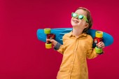 adorable smiling little skater in sunglasses posing with penny board isolated on red