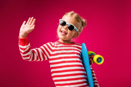 excited stylish kid in sunglasses holding penny board and waving isolated on red