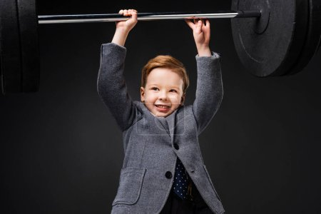 strong smiling little boy in suit lifting barbell isolated on grey