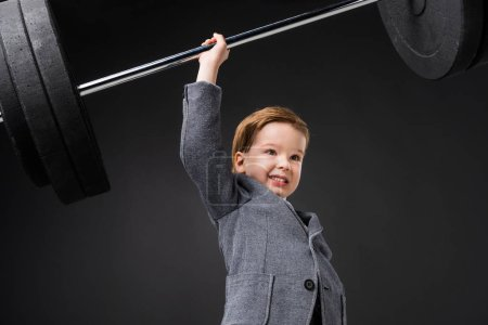 strong cheerful boy in suit lifting barbell isolated on grey