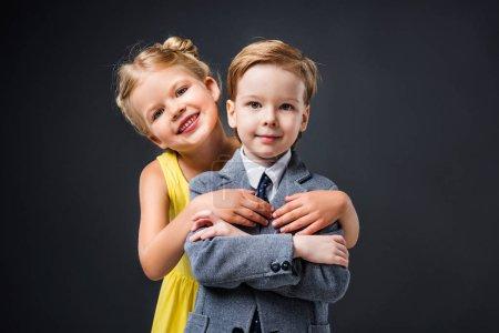 happy little couple hugging isolated on grey