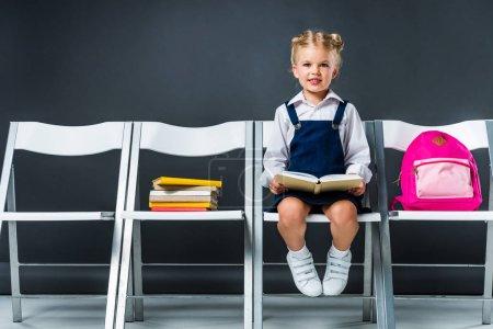 Photo pour Adorable écolière assise sur des chaises avec des livres et un sac à dos - image libre de droit