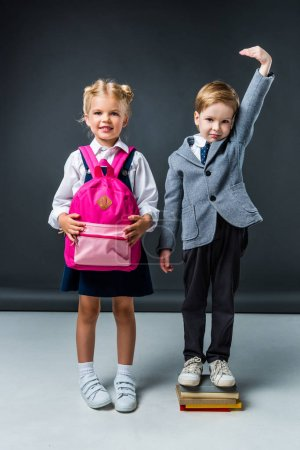 adorable schoolboy standing on books to be higher near smiling schoolgirl with pink backpack