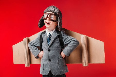excited boy in suit with paper plane wings and goggles isolated on red