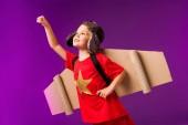 ailes de gamin souriant avec plan et lunettes debout avec les bras tendu à voler isolement sur violet