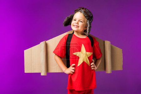 little cheerful pilot with cardboard plane wings and goggles isolated on purple