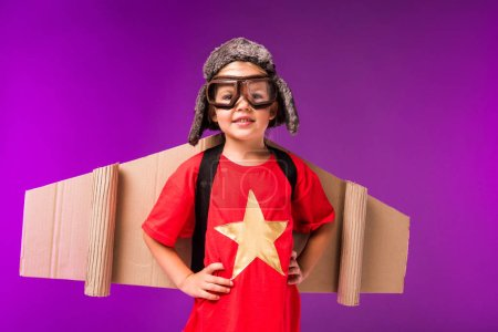 happy child with paper plane wings, hat and protective goggles isolated on purple