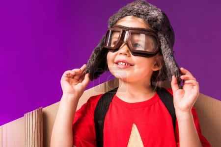 smiling child with paper plane wings and protective eyeglasses isolated on purple