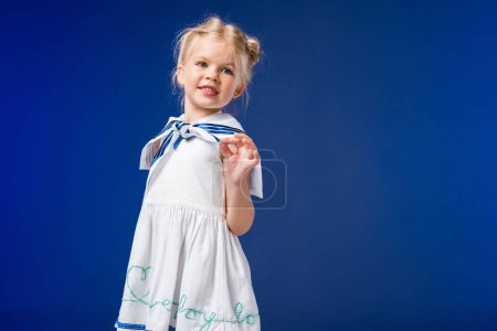 adorable blonde kid posing in sailor costume, isolated on blue