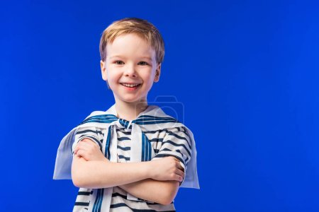smiling boy posing in striped t-shirt with crossed arms, isolated on blue