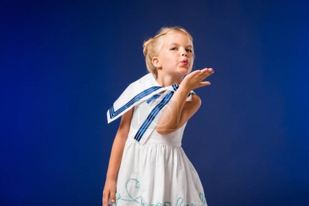 adorable blonde child in sailor costume blowing kiss, isolated on blue