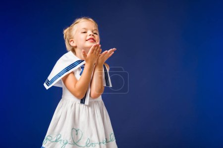 adorable happy kid in sailor costume blowing kiss, isolated on blue
