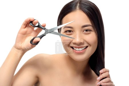 portrait of smiling asian woman with scissors isolated on white, damaged hair and split ends concept