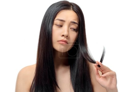 portrait of upset asian woman looking at split ends isolated on white, damaged hair concept