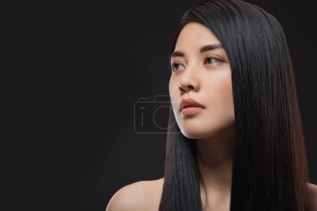 portrait of pensive asian woman with healthy and strong hair isolated on black