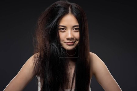 portrait of smiling asian woman with half knotted and straight hair isolated on black, keratin hair treatment concept