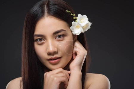 portrait of beautiful young asian woman with white flowers in hair looking at camera isolated on black
