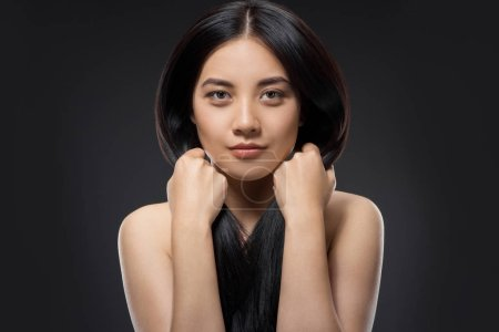 portrait of pretty asian woman with healthy and strong hair looking at camera isolated on black