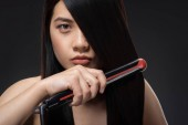 portrait of young asian woman straightening hair with hair straightener isolated on black
