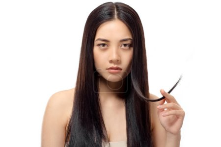 portrait of young asian woman with split ends looking at camera isolated on white, damaged hair concept
