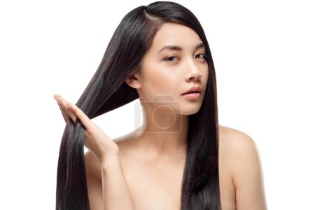portrait of attractive asian model with strong and healthy hair looking at camera isolated on white