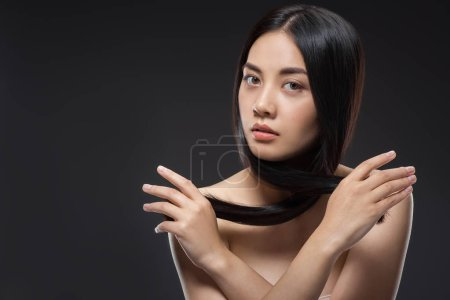 Photo for Portrait of young asian woman with beautiful and healthy dark hair looking at camera isolated on black - Royalty Free Image