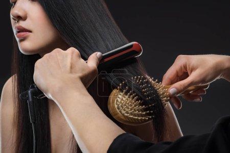 Photo pour Vue partielle du coiffeur lissant womans cheveux avec lisseur et brosse isolée sur noir - image libre de droit