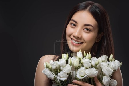 portrait of asian woman with beautiful dark hair and bouquet of white eustoma flowers isolated on black