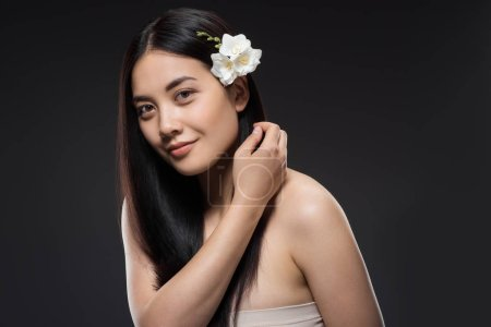 portrait of beautiful young asian woman with white flowers in hair isolated on black