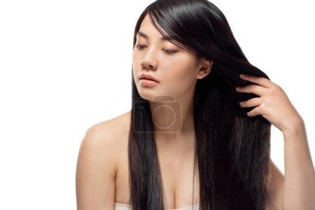 Retrato de atractivo modelo asiático con pelo fuerte y sano busca a aislado en blanco