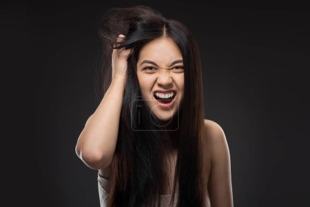 portrait of emotional asian woman with dark healthy hair isolated on black
