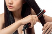 partial view of woman straightening hair with hair straightener isolated on white