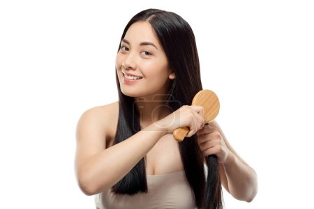 portrait of smiling beautiful asian woman brushing hair isolated on white