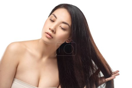 portrait of asian model with healthy and shiny hair posing isolated on white