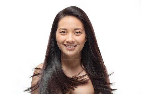 portrait of smiling asian woman with beautiful and healthy hair isolated on white