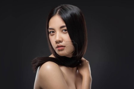 Photo for Portrait of young asian woman with beautiful and healthy dark hair posing isolated on black - Royalty Free Image