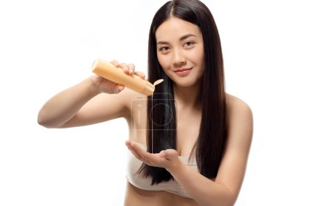 portrait of young asian woman pouring shampoo in hand isolated on white, hair treatment concept