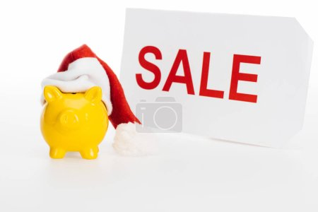 yellow piggy bank in santa hat and sale sign isolated on white