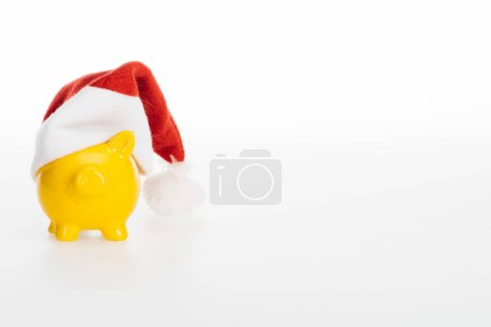 yellow piggy bank in santa hat isolated on white background