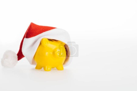 close-up view of yellow piggy bank in santa hat isolated on white