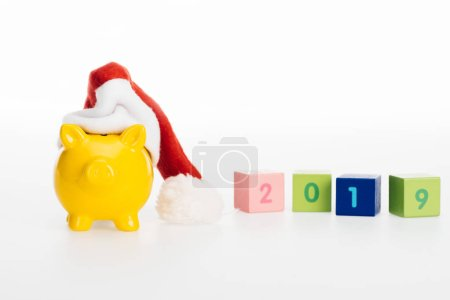 close-up view of 2019 symbol on cubes, yellow piggy bank and santa hat isolated on white