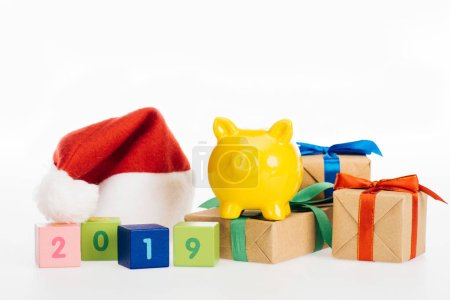 close-up view of 2019 symbol on cubes, yellow piggy bank, gift boxes and santa hat isolated on white