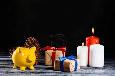 Photo pour Tirelire jaune, pommes de pin, cadeaux de Noël et bougies brûlants - image libre de droit