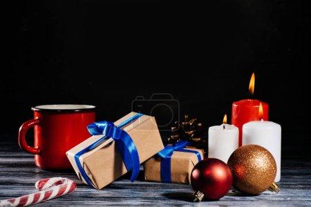 Photo pour Vue rapprochée de brûler des bougies, cône du pin, boules de Noël et des cadeaux sur la table en bois sur fond noir - image libre de droit