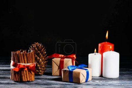 close-up view of burning candles, pine cone and christmas gifts on wooden table on black