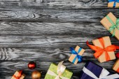 top view of christmas gifts and shiny baubles on wooden surface