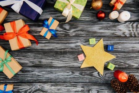 Photo pour Vue de dessus de Noël présente, signe de 2019, étoiles et brûlante des bougies sur une surface en bois - image libre de droit